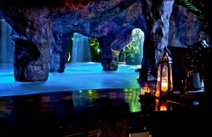 A handmade faux rock grotto features a swim-through entrance and utilizes color kinetics lighting for dramatic effect. Photo courtesy Caviness Landscape Design.