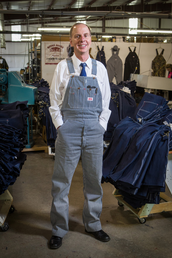 Round House CEO Jim Antosh displays the company's iconic overalls. Photo by Brent Fuchs.