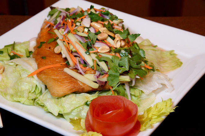 The Pla Song Kraung boasts a crispy fried whole trout filled and topped with shredded green apple, red onion, carrots, lettuce and peanuts. Photo by Natalie Green.