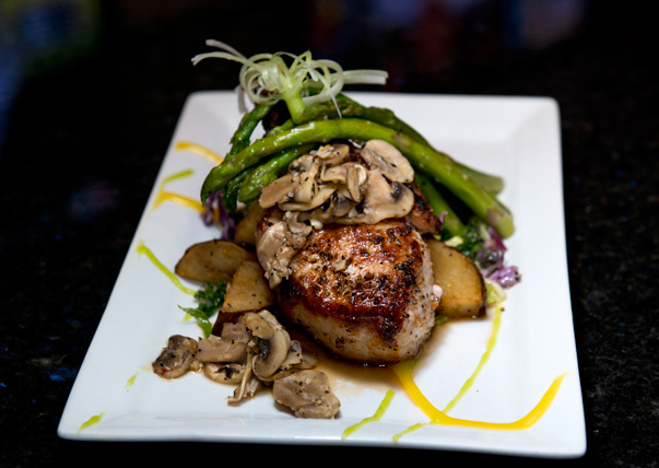 Grilled pork chop is topped with mushrooms and asparagus at Off The Cuff. photo by Natalie Green.