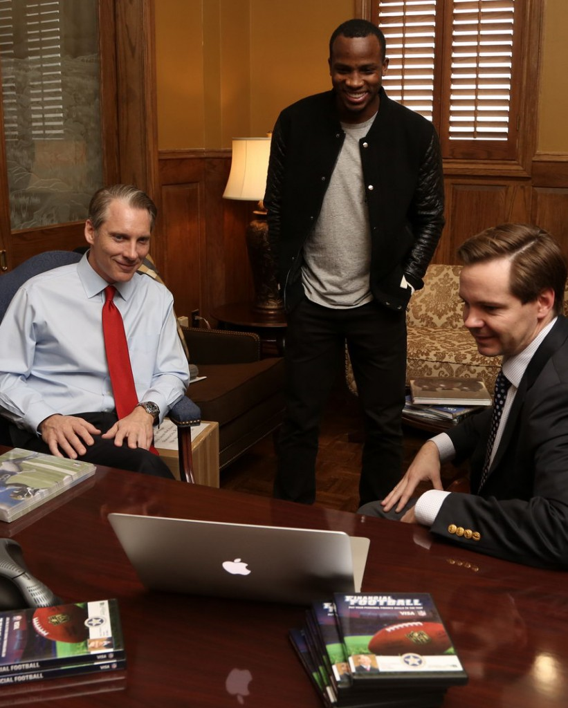 : State Treasurer Ken MIller, former OU and current NFL player Ryan Broyles, and Nat Sillin of Visa Inc. watch a demonstration of Financial Football, a video game to help student learn basic financial skills. The three announced release of the game in the State Treasurer's Office at the State Capitol on Wednesday morning. Photo by : Travis Caperton, Capitol Photographer.
