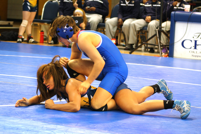 Oklahoma City Univeristy wrestler Emily Webster (top) grapples with an opponent during the 2013-2014 season. Photo by Rich Tortorelli.