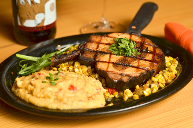 Chorizo and cornbread stuffed pork chop with skillet corn and hominy grits. Photo by Dan Morgan.