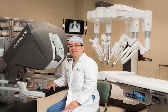Dr. Peter Baik, a thoracic surgeon with CTCA sitting in a surgery suite with the Da Vinci Xi System.